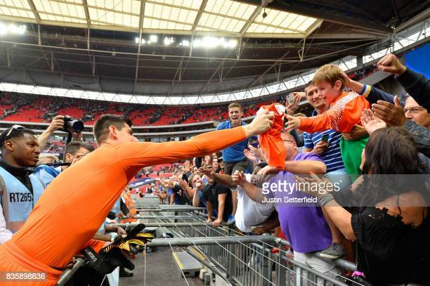 Thibaut Courtois of Chelsea gives his match shirt to a young Chelsea fan in the crowd after the Premier League match between Tottenham Hotspur and...