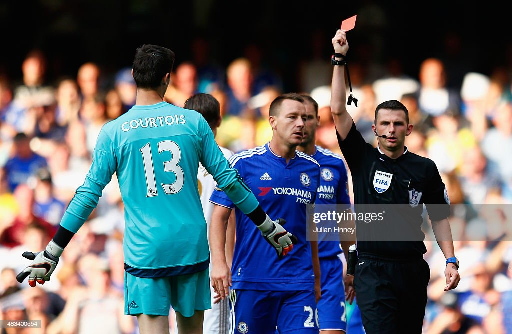 Thibaut Courtois (L) of Chelsea is shown the red card by referee Michael Oliver (R) during the Barclays Premier League match between Chelsea and Swansea City at Stamford Bridge on August 8, 2015 in London, England.