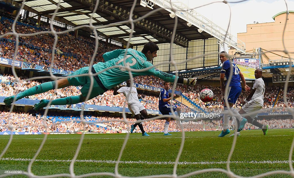 Thibaut Courtois of Chelsea makes a save from Bafetibis Gomis of Swansea City during the Barclays Premier League match between Chelsea and Swansea City at Stamford Bridge on August 8, 2015 in London, England.