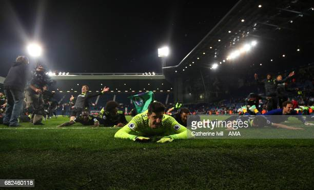 Thibaut Courtois of Chelsea slides on the pitch as he celebrates winning the Premier League during the Premier League match between West Bromwich...