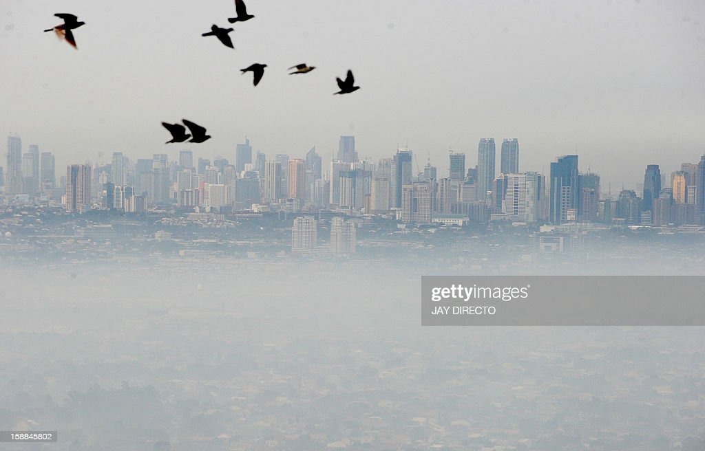 A thick blanket of smog covers an eastern section of the Philippine capital Manila on January 1, 2013 the morning after millions across the nation set off firecrackers and pyrotechnics to welcome in the New Year. In the capital Manila, authorities had been bracing for the annual rush of injuries as families celebrated with do-it-yourself firework displays and shot celebratory bullets into the air.