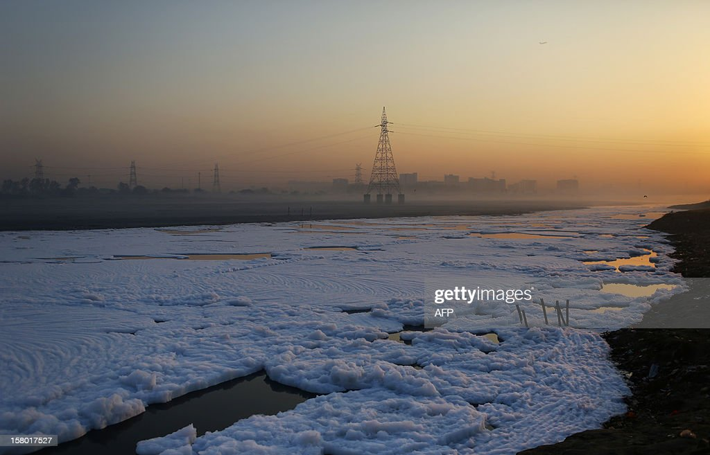 Thick foam flows down the polluted Yamuna river in New Delhi at dawn on December 9, 2012. India's Supreme Court said on December 8, all parameters of water quality of river Yamuna indicate that it resembles a drain and urged authorities to make it pollution-free. Over 2,400 million liters of untreated sewage flows into the Yamuna every day. AFP PHOTO/ Andrew Caballero-Reynolds