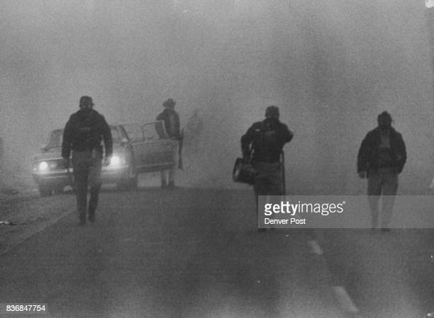 Thick fog added an eerie aura at Brighton flower farm of Kitayama Brothers as deputy sheriffs in gas masks strode from patrol cars toward pickets at...