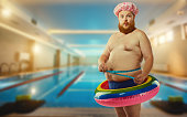 Fat funny man in the inflatable circle in the pool.