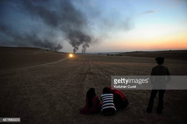 Thick smoke raises from the Syrian town of Kobani as a people watch the fighting between Islamic State militants and Kurdish People's Protection Unit...