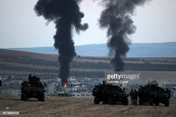 Thick smoke raises from the Syrian town of Kobani as Turkish soldiers stand guarded in the Turkish side of the border during fighting between Islamic...