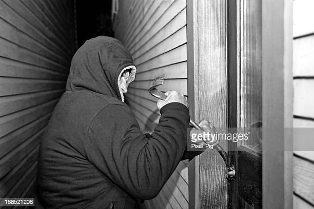 Thief breaking into Home with Crowbar - black and white