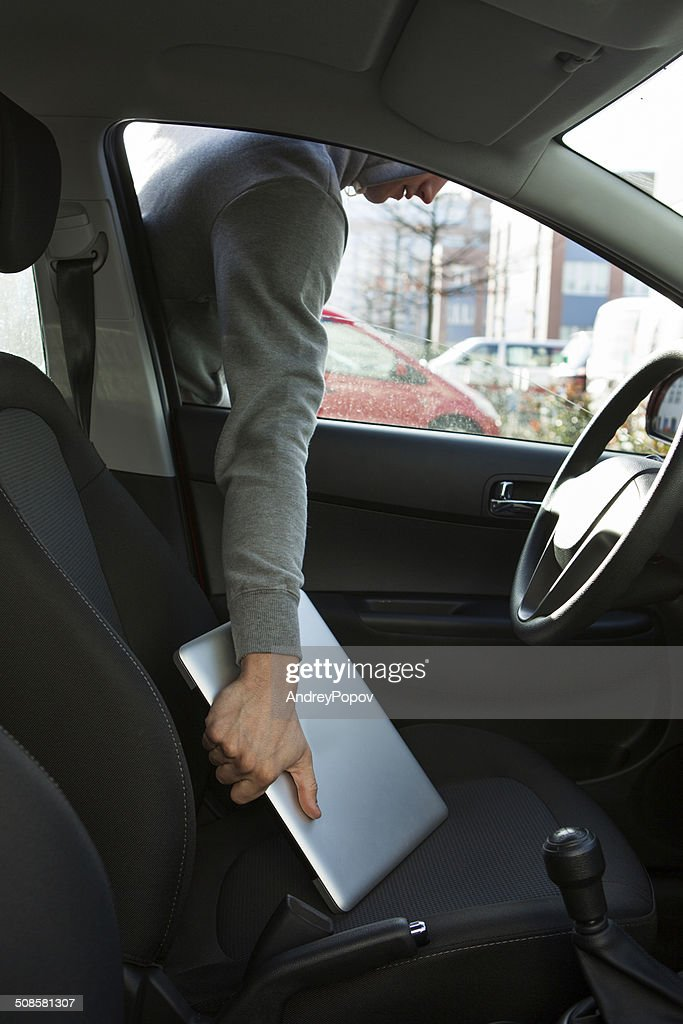 Thief Stealing Laptop Through Car Window : Stockfoto