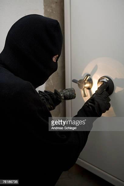A thief unlocking a combination safe