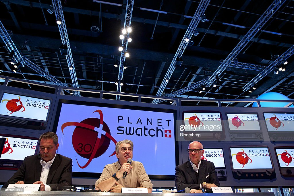 Thierry Conus, director of research and development at ETA SA Manufacture Horlogere Suisse, left, Nick Hayek, chief executive officer of Swatch Group AG, and Carlo Giordanetti, creative director of Swatch Group AG, attend a news conference to launch the Sistem51 automatic watch movement, during the Baselworld watch fair in Basel, Switzerland, on Thursday, April 25, 2013. The annual fair attracts 2,000 companies from the watch, jewelry and gem industries to show their new wares to more than 100,000 visitors. Photographer: Gianluca Colla/Bloomberg via Getty Images