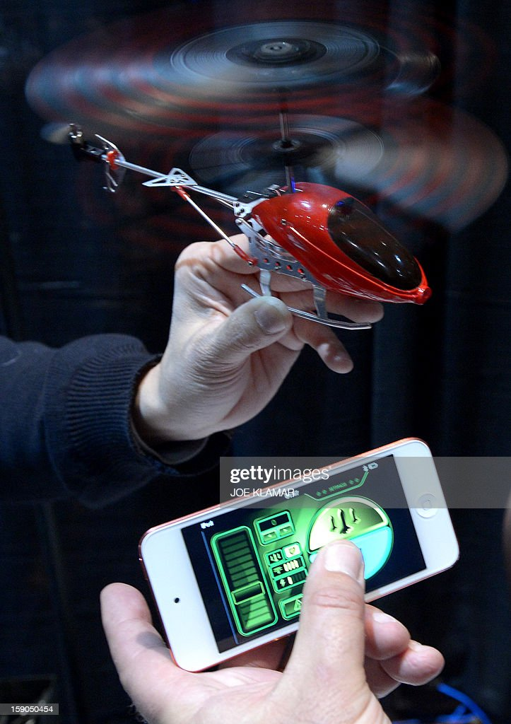 Thierry Dechatre of Avenir Telecom shows BeWii bluetooth operated heliccopter by iPhone during the opening event ''CES Unveiled'' during the International Consumer Electronics Show (CES) in Mandalay Bay Hotel resort on January 06, 2013 in Las Vegas, Nevada.AFP PHOTO / JOE KLAMAR