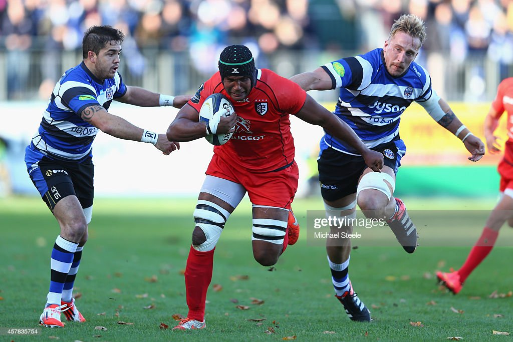 Thierry Dusautoir (C) of Toulouse breaks through the challenge of Dominic Day (R) and Horacio Agulla (L) of Bath during the European Rugby Champions Cup Pool Four match between Bath Rugby and Toulouse at the Recreation Ground on October 25, 2014 in Bath, England.