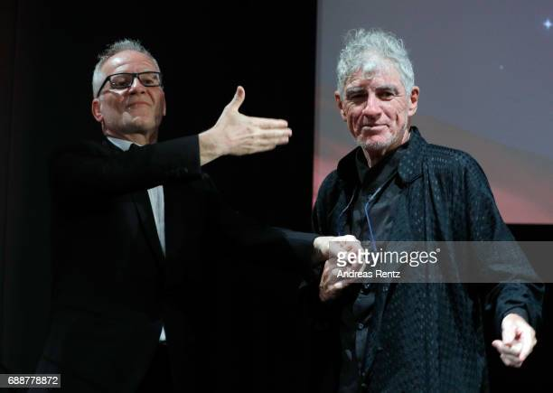 Thierry Fremaux and Christopher Doyle greet each other on stage during the Tribute to Christopher Doyle during the 70th annual Cannes Film Festival...