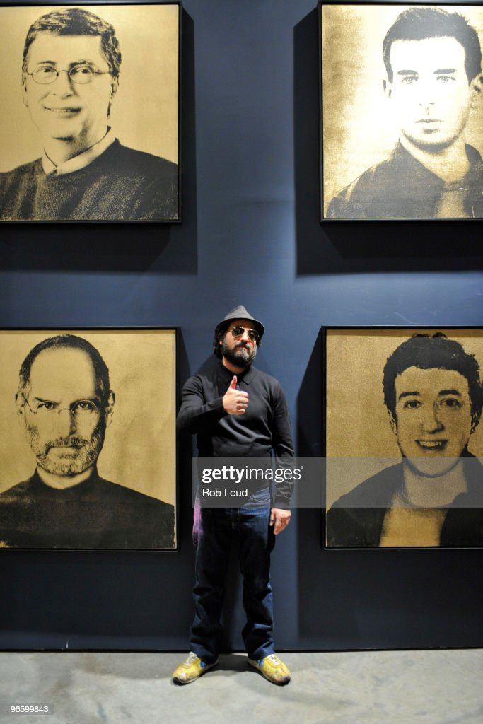 Thierry Guetta, aka Mr. Brainwash, poses in front of his artwork at his solo exhibition opening on February 11, 2010 in New York City.