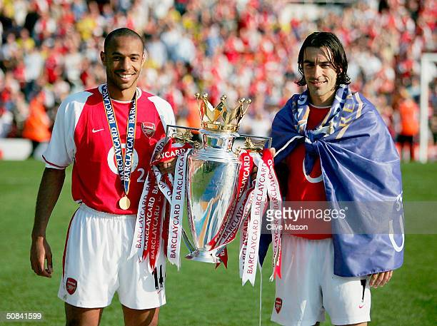 Thierry Henry and Robert Pires of Arsenal hold the Premiership trophy during the celebrations as they celebrate winning the Premiership during the FA...
