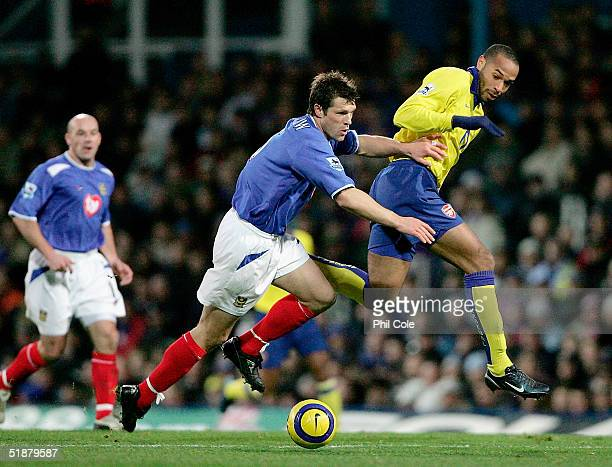 Thierry Henry of Arsenal battles with Arjan De Zeeuw of Portsmouth during the Barclays Premiership match between Portsmouth and Arsenal at Fratton...