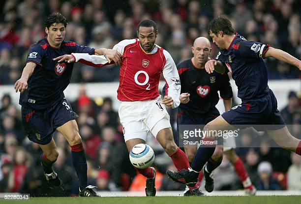 Thierry Henry of Arsenal breaks through Dejan Stefanovic and Arjan De Zeeuw of Portsmouth during the Barclays Premiership match between Arsenal and...