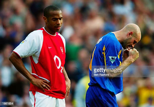 Thierry Henry of Arsenal looks dejected after they lose the match and championship as Danny Mills of Leeds United celebrates a vital win to keep them...
