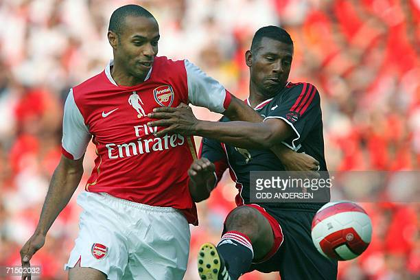 Thierry Henry of Arsenal scores a goal despite the efforts of Aron Winter of Ajax during a pre season 'Dennis Bergkamp' testimonial match at Emirates...