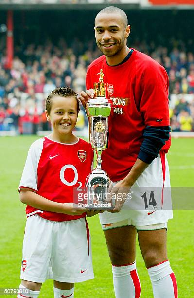 Thierry Henry of Arsenal with his PFA Player Of The Year award alongside the Arsenal mascot prior to kickoff during the FA Barclaycard Premiership...