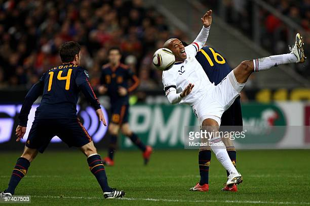 Thierry Henry of France is challenged from Sergio Busquets of Spain as Xabier Alonso watches during the France v Spain International Friendly match...