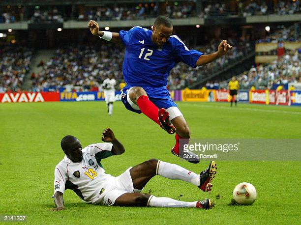 Thierry Henry of France is tackled by Lucien Mettomo of Cameroon during the FIFA Confederations Cup Final between France and Cameroon held on June 29...