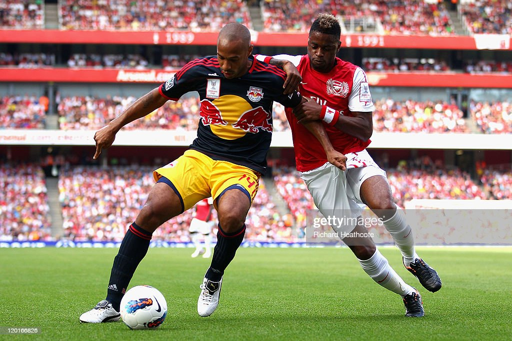 Thierry Henry of New York Red Bulls and Alex Song of Arsenal battle for the ball during the Emirates Cup match between Arsenal and New York Red Bulls...