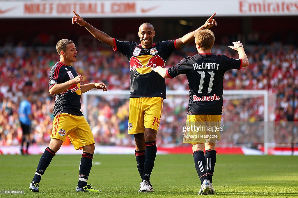 Thierry Henry of New York Red Bulls celebrates with team mates John Rooney and Dax McCarty after Kyle Bartley of Arsenal scores an own goal during...