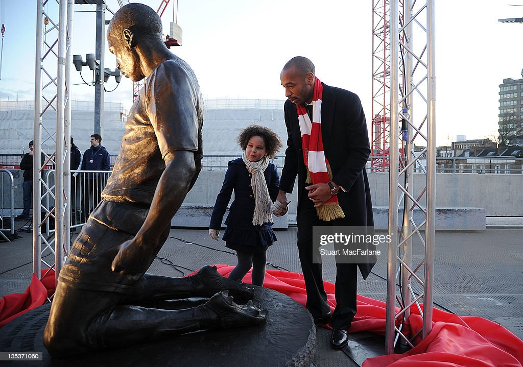 Thierry Henry with daughter Tea after a statue of him is unveiled at Emirates Stadium, one of three iconic statues to be placed at the Emirates Stadium home of Arsenal Football Club, on December 9, 2011 in London, England.