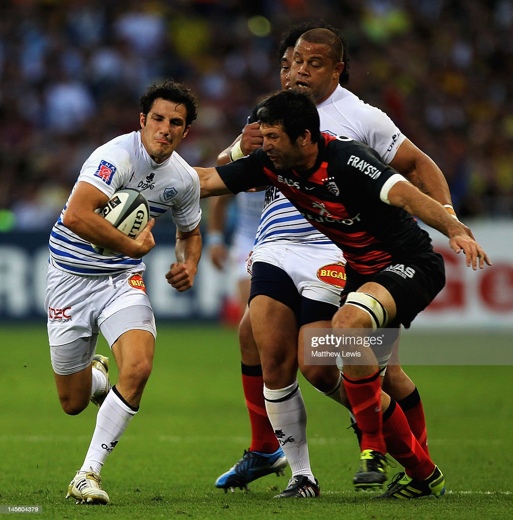 Thierry Lacrampe of Castres beats the tackle from <a gi-track='captionPersonalityLinkClicked' href=/galleries/search?phrase=Jean+Bouilhou&family=editorial&specificpeople=572048 ng-click='$event.stopPropagation()'>Jean Bouilhou</a> of Toulouse during the French Top 14 Semi Final match between Toulouse and Castres Olympique at Stade de Toulouse on June 2, 2012 in Toulouse, France.