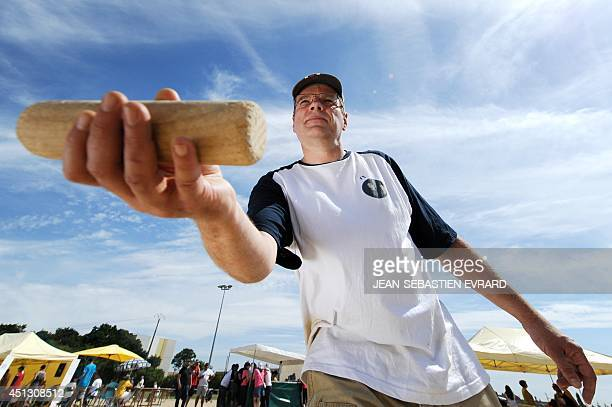 Thierry Pannetier holds a skittle before throwing it while playing Molkky on June 21 2014 in L'Hermitage western France The Molkky is a skittle game...
