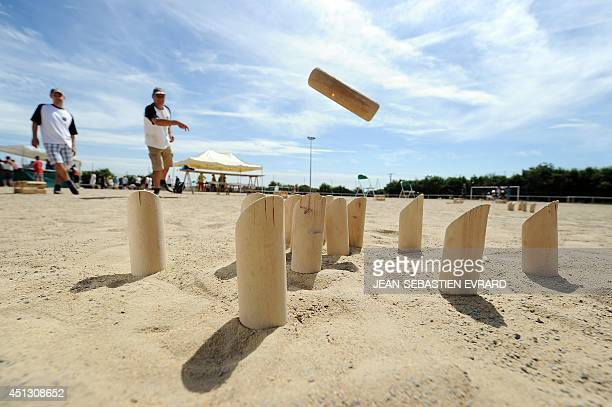 Thierry Pannetier throws a skittle while playing Molkky on June 21 2014 in L'Hermitage western France The Molkky is a skittle game created by the...