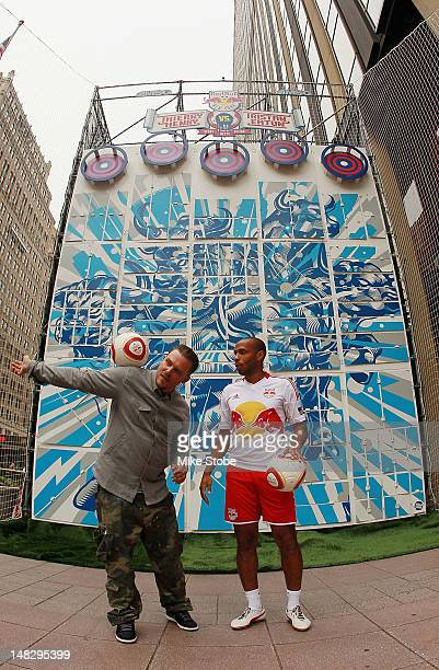 Thiery Henry of the New York Red Bulls and pop artist Tristan Eaton pose for a photo after Henry succesfully kicked a soccer ball at targets to...