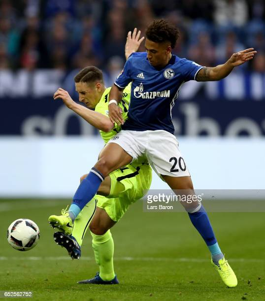 Thilo Kehrer of Schalke battles for the ball with Dominik Kohr of Augsburg during the Bundesliga match between FC Schalke 04 and FC Augsburg at...