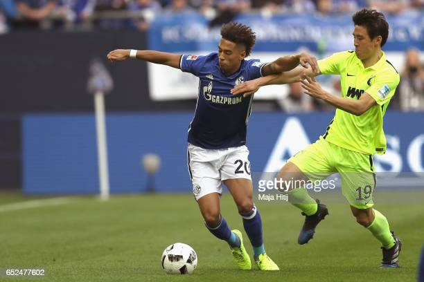 Thilo Kehrer of Schalke battles for the ball with JaCheol Koo of Augsburg during the Bundesliga match between FC Schalke 04 and FC Augsburg at...