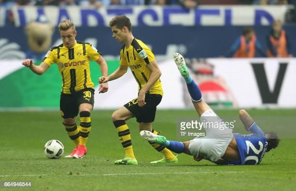 Thilo Kehrer of Schalke faellt neben Julian Weigl of Dortmund and Felix Passlack battle for the ball during the Bundesliga match between FC Schalke...