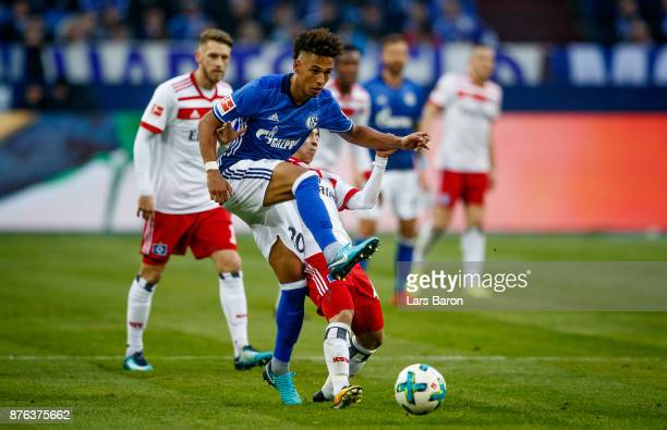 Thilo Kehrer of Schalke is challenged by Tatsuya Ito of Hamburg during the Bundesliga match between FC Schalke 04 and Hamburger SV at VeltinsArena on...