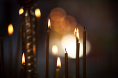 Burning candles in the church on the background of a side of other candles