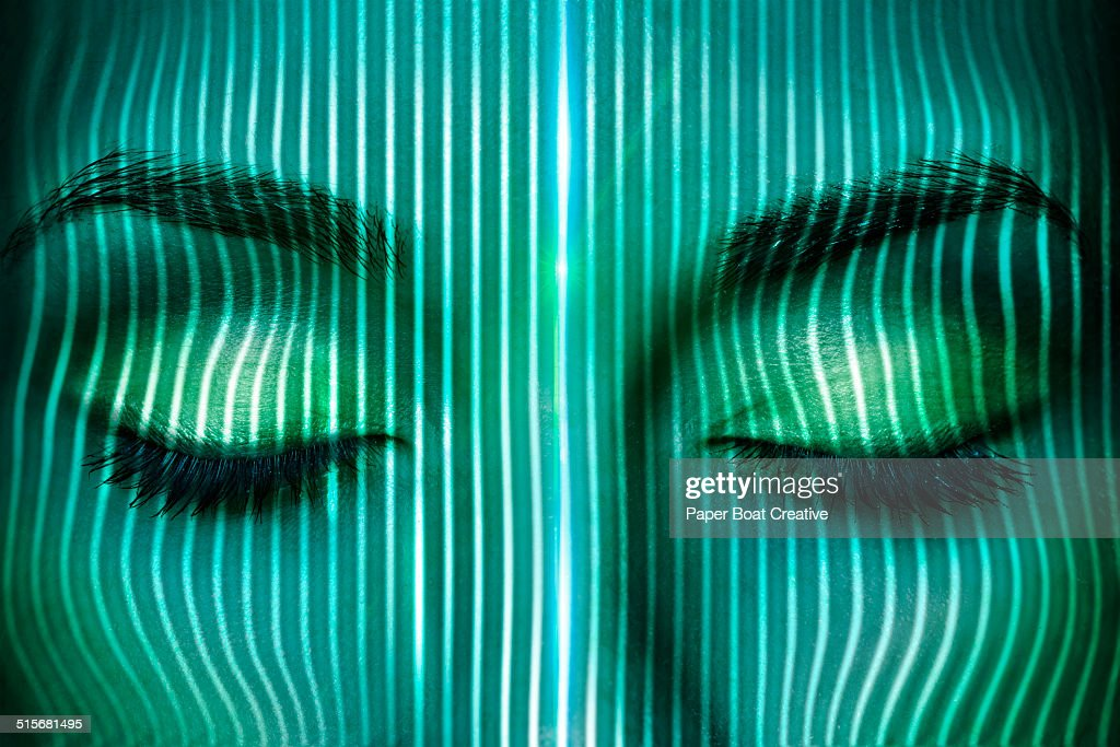Thin laser beams going over a woman's face : Stock Photo