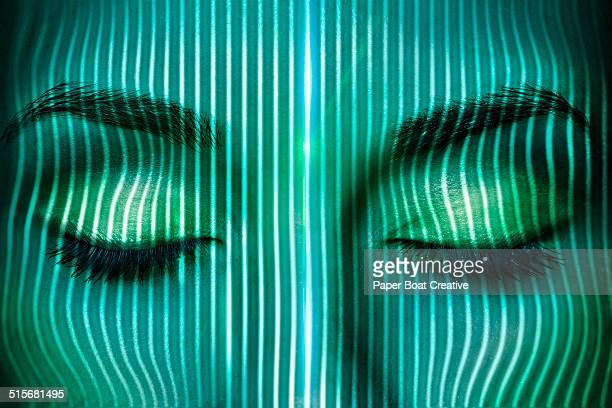 Thin laser beams going over a woman's face