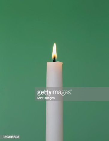 lit candle white background. a thin white wax candle with small lit flame green background stock photo   getty images l