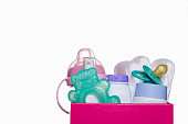 things for the baby in the box: diapers, bottle, cream, toy, nipple. Isolated on white background. place for text