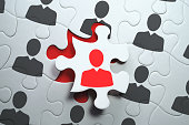 Jigsaw puzzle piece with red businessperson standing out from the crowd.