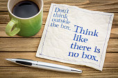 Don't think outside the box. Think like there is no box.- handwriting on a napkin with a cup of espresso coffee