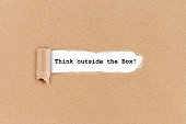 think outside the box business concept ripped hole in brown paper on white background