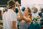 Young couple are exploring Queen Victoria Market in Australia. The woman is putting a hat on her boyfriend in a market stall.