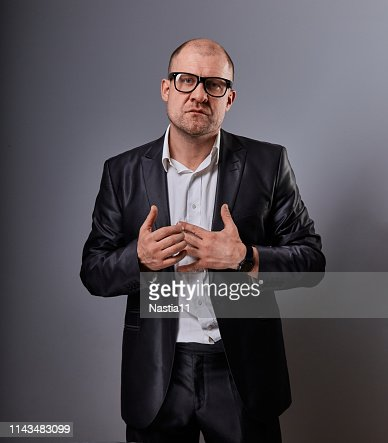 Thinking bald business man holding the chest two hands with serious face in eyeglasses in suit on grey background. Closeup : Stock Photo