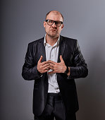 Thinking bald business man holding the chest two hands with serious face in eyeglasses in suit on grey background. Closeup portrait