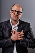 Thinking bald business man holding the chest two hands with serious face and closed eyes in eyeglasses in suit on grey background. Closeup portrait