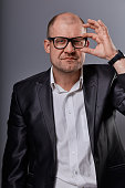 Thinking bald business man looking serious in eyeglasses in suit on grey background. Closeup portrait